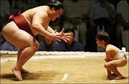 A Sumo Wrestler Facing-Off against a Toddler